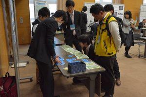 本学大学院生が開発したカードゲーム教材をプレゼンする様子