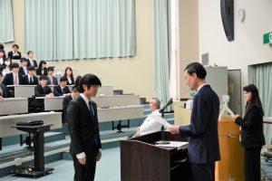 内木医学部長から認定証を受ける学生代表の三田英貴さん