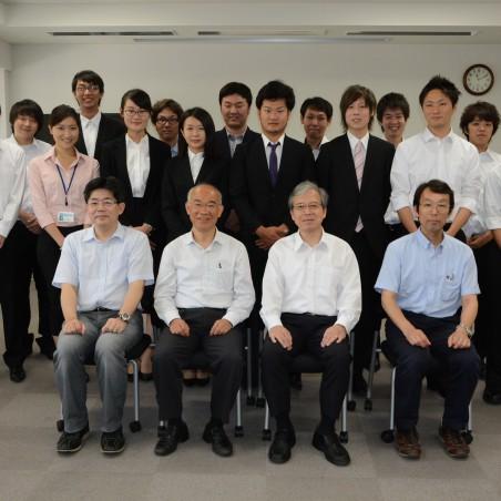 「工学研究科長と担当教職員および修了生による集合写真」