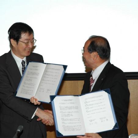 調印後、にこやかに握手を交わす福田学長と黒田福井県眼鏡工業組合理事長