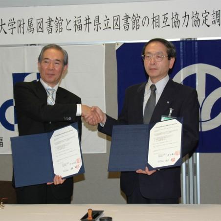 相互協力協定に調印後、握手を交わす桂屋県立図書館長と中川附属図書館長